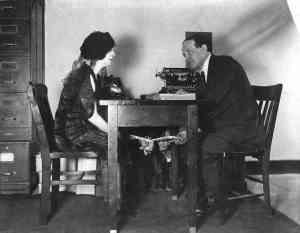 Houdini e Besss mostrando como era feito o truque da escrita fantasma (repare que há alguéme scondido debaixo da mesa)
